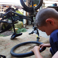 Kai changing his bike tyre after a run in with <i>bindies</i>.
